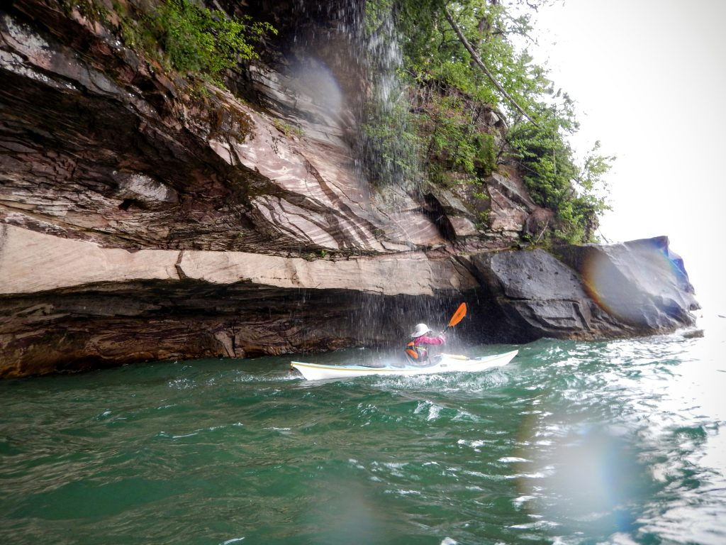 Paddling under a waterfall on the Pictured Rocks